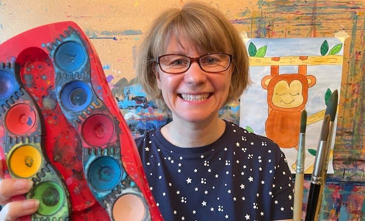 Diana Schalthöfer lächelt in die Kamera und hält einen Wasserfarben-Malkasten ins Bild.