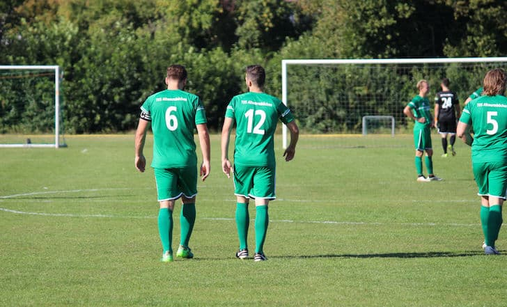 Foto von zwei Spielern der Ersten Herrenmannschaft. Sie laufen über den Fußballplatz, Bild ist von hinten aufgenommen.
