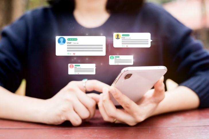 Bild zeigt eine Person, die am Smartphone sitzt und sich Online-Bewertungen anschaut. Diese sind ebenfalls als Grafik im Bild sichtbar.