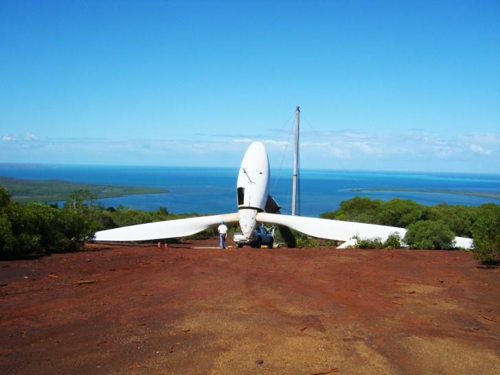 Bauarbeiter errichten eine Windkraftanlage auf Neukaledonien. Im Vordergrund sieht man rote Erde und eine liegende Windkraftanlage, im Hintergrund grüne Vegetation und das türkisblaue Meer, sowie blauen Himmel.